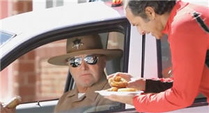 Carlos Alcántara ofrece un picarón a un sheriff de Nebraska
