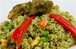 Imagen de un sabroso plato peruano de arroz con pollo, con arvejas, zanahorias y pimiento.