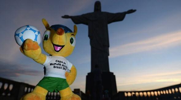 Foto del muñeco Fuleco junto al Cristo de Corcovado en Brasil