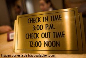 Rótulo dorado con horarios check in y check out en hotel
