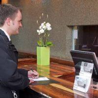 Huésped en la recepción de un hotel en proceso de check in