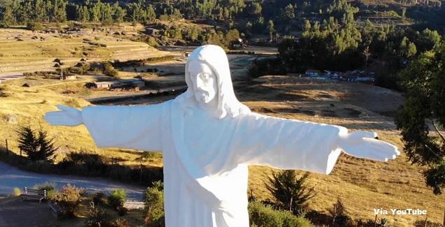 Foto de campos verdes y en el medio el Cristo Blanco de Cusco en Perú.