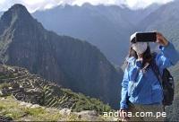 Imagen de mujer turista con tapaboca, tomándose selfie en Machu Picchu (andina.com.pe)