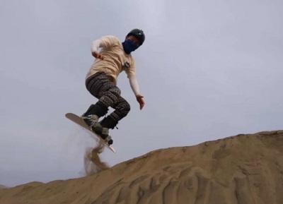 Turista practicando sandboarding en las dunas de Chilca